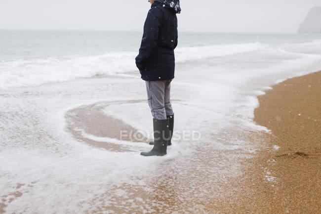 Adolescente ragazzo in gomma stivali in piedi in nevoso inverno oceano surf — Foto stock
