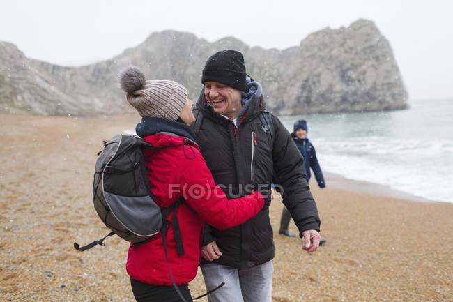Affettuosa, coppia felice in abiti caldi sulla spiaggia invernale innevata — Foto stock