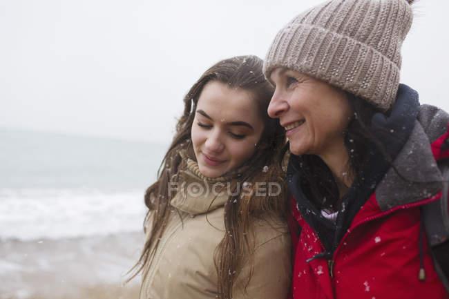 Affettuosi madre e figlia sulla spiaggia invernale innevata — Foto stock