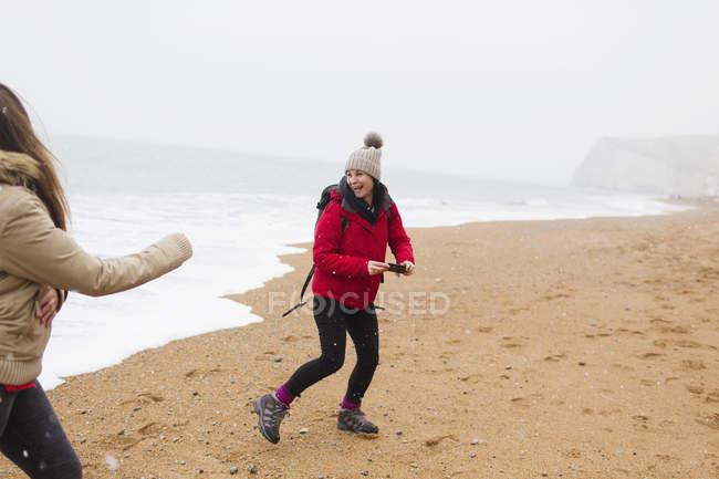 Madre giocherellona e figlia sulla spiaggia invernale dell'oceano — Foto stock