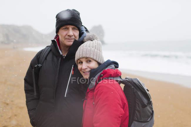 Coppia di ritratti in abiti caldi sulla spiaggia invernale — Foto stock