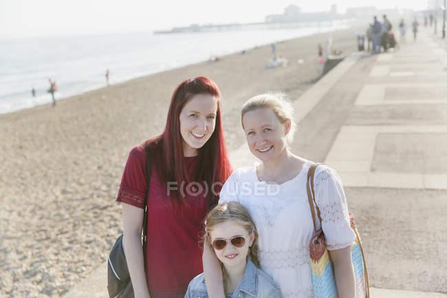 Lächelnde lesbisches Paar Porträt und Tochter am sonnigen Strand-Promenade — Stockfoto