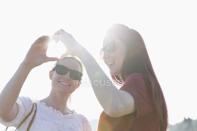 Cariñosa pareja de lesbianas formando forma de corazón con manos - foto de stock