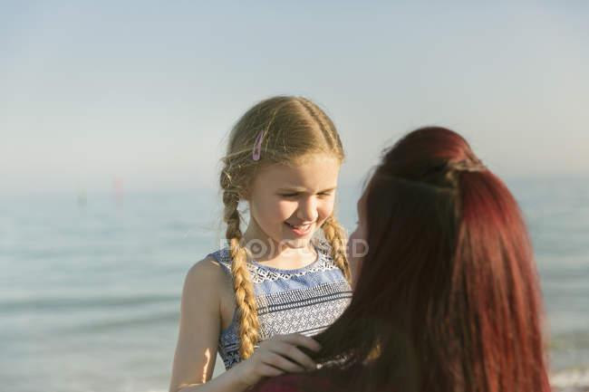 Ласкава мати холдингу дочку на пляжі сонячні океану — стокове фото