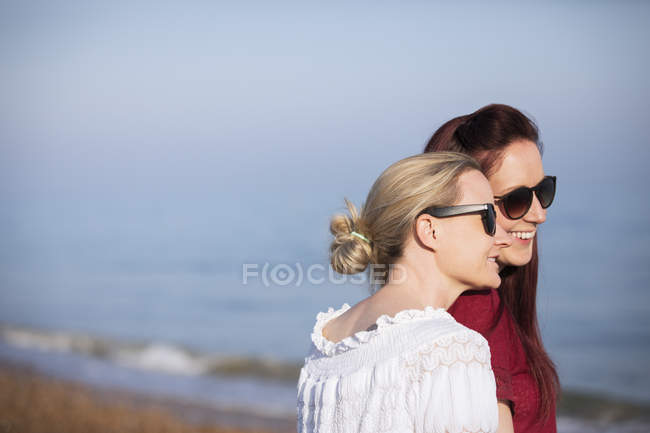 Affectionate lesbian couple on sunny beach — Stock Photo