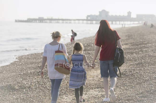 Coppia lesbica e figlia a piedi sulla spiaggia soleggiata — Foto stock