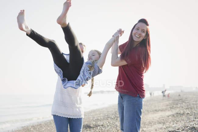 Spielerische lesbisches Paar swingenden Tochter am Strand — Stockfoto