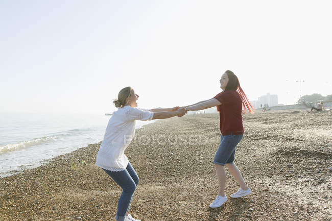 Playful lesbian couple holding hands and spinning on sunny beach — Stock Photo