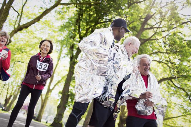 Активные старшеклассники заканчивают спортивную гонку, завернутые в тепловые одеяла — стоковое фото