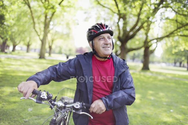 Aktiven senior Mann Reiten Fahrrad im park — Stockfoto