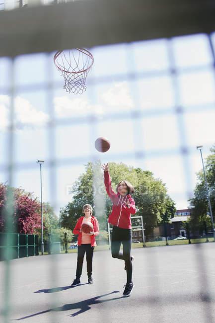 Активные пожилые женщины играют в баскетбол в солнечном парке — стоковое фото