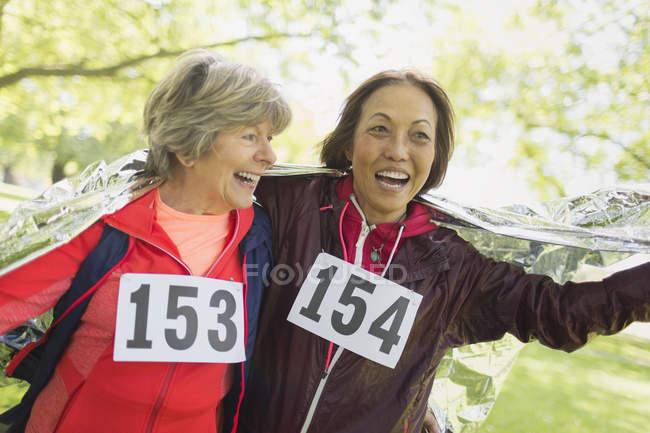 Счастливые активные пожилые женщины заканчивают спортивную гонку, завернутые в тепловое одеяло — стоковое фото