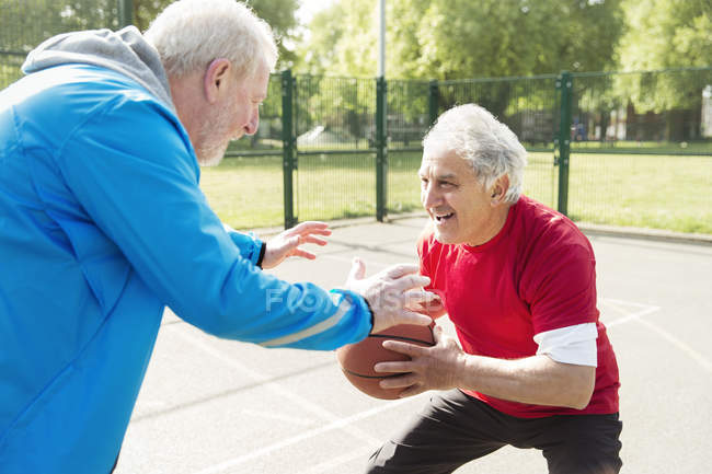 Hombres mayores activos amigos jugando baloncesto en el soleado parque - foto de stock
