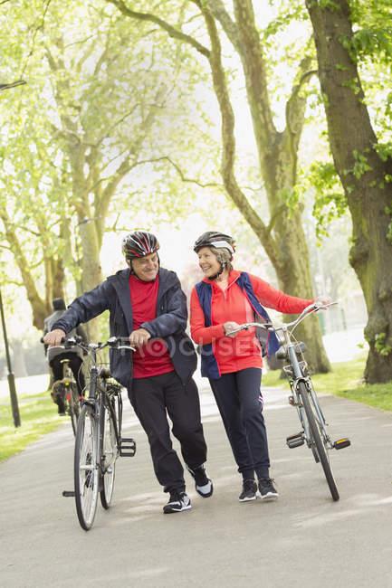 Активная старшая пара пеших велосипедов в парке — стоковое фото