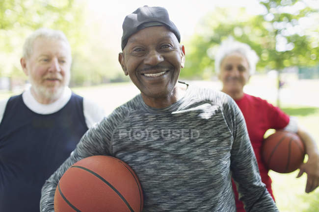 Ritratto fiducioso, sorridente gli amici uomini senior attivi con palloni da basket nel parco — Foto stock