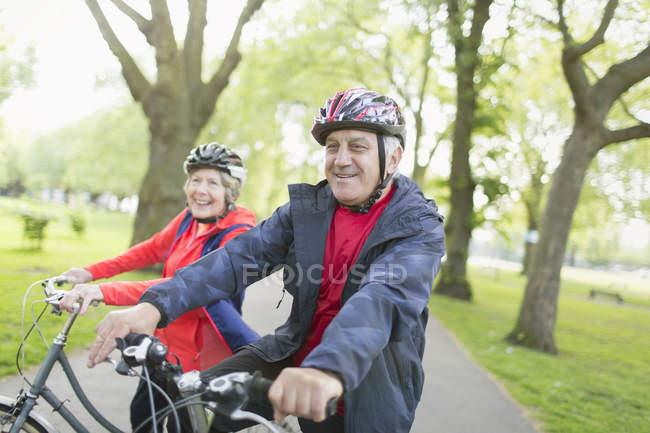 Active senior couple riding bikes in park — Stock Photo