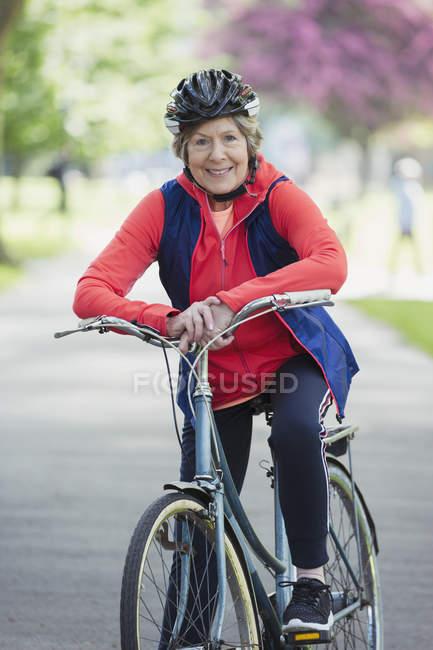 Портрет улыбается, уверенная в себе активная старшая женщина на велосипеде в парке — стоковое фото