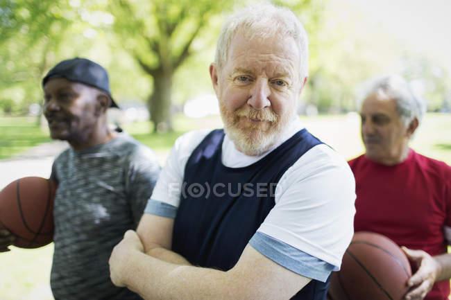 Selbstbewusster aktiver Senior spielt mit Freunden Basketball — Stockfoto