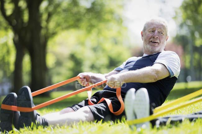 Hombre mayor activo haciendo ejercicio en el parque, estirándose con banda de resistencia - foto de stock