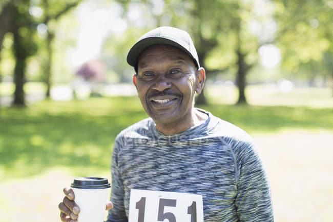 Портрет улыбающийся, уверенный в себе активный пожилой мужчина пьет кофе перед спортивной гонкой в парке — стоковое фото