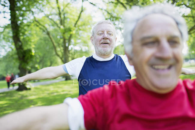 Active senior men exercising, stretching in park — Stock Photo