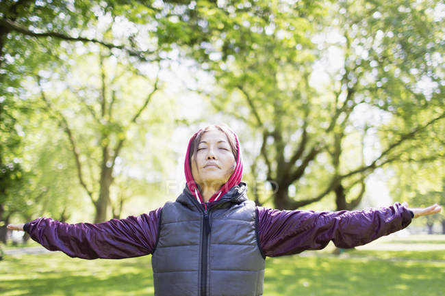 Portrait serene active senior woman stretching in park — Stock Photo