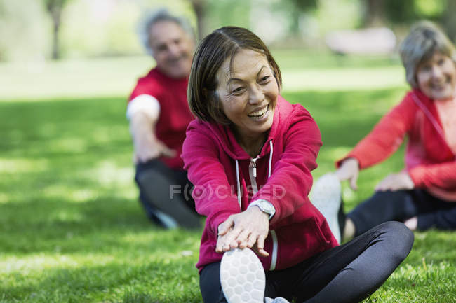 Happy active senior woman stretching leg in park — Stock Photo