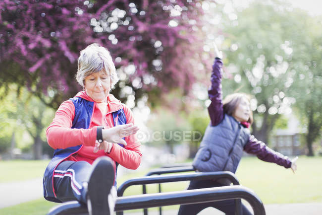 Active senior female runner stretching leg and checking smart watch — Stock Photo