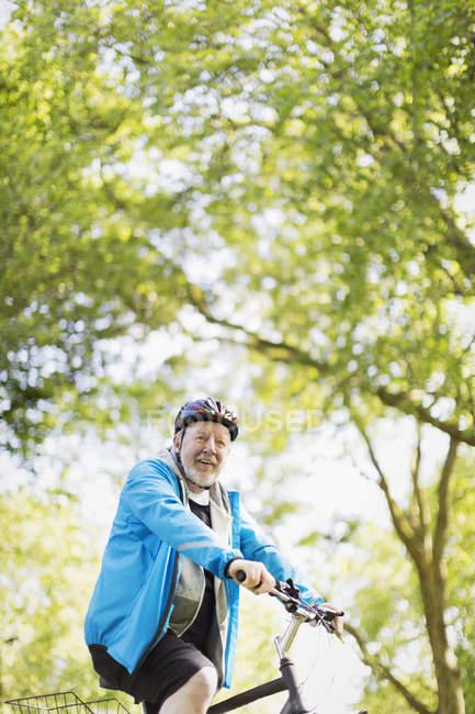 Портрет уверенный в себе активный старший мужчина на велосипеде в парке — стоковое фото