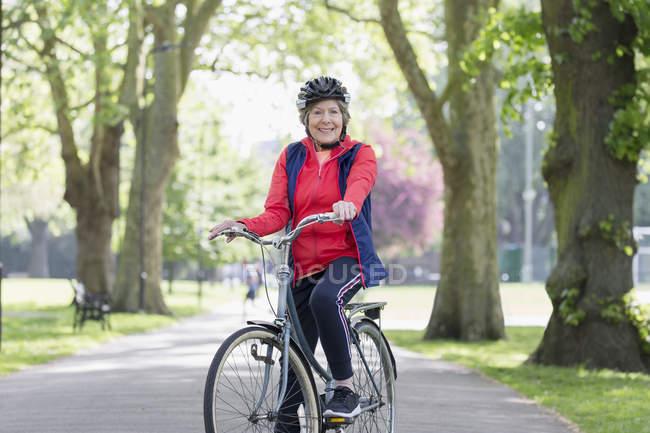 Портрет уверенно активная старшая женщина на велосипеде в парке — стоковое фото