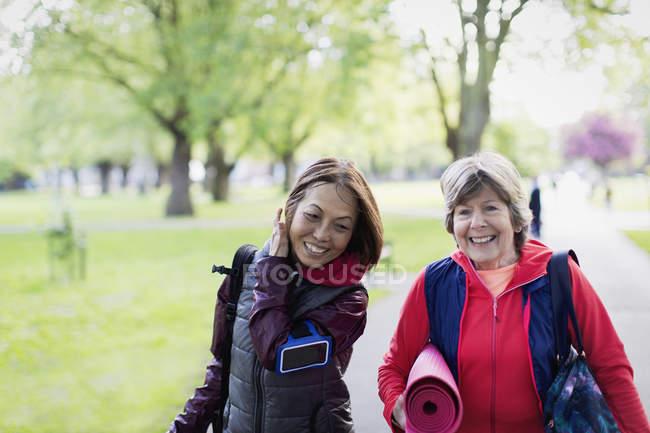 Активні старші жінки друзі з йога килимок, прогулянки в парку — стокове фото