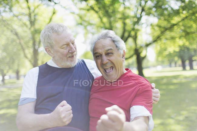 Ausgelassene aktive Senioren-Freunde jubeln im Park — Stockfoto