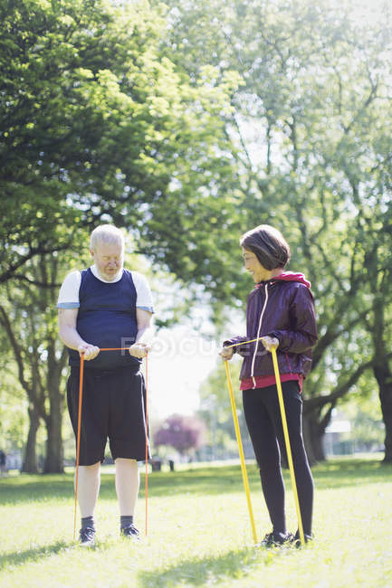 Active senior couple exercising, stretching with resistance bands in sunny park — Stock Photo