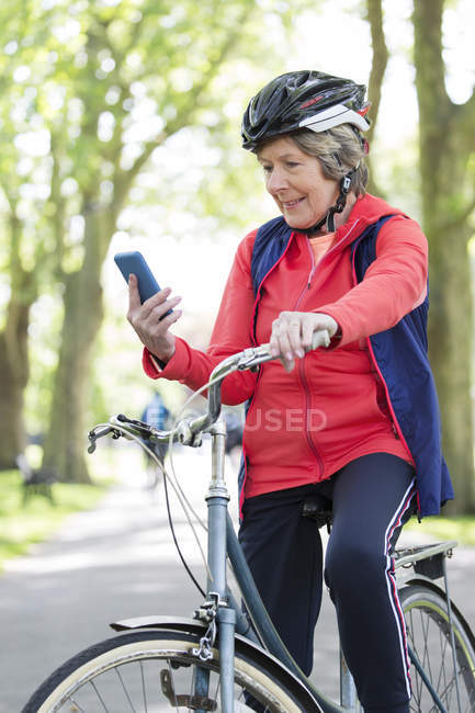 Active senior woman using smart phone on bike in park — Stock Photo