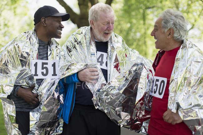 Активные старшие друзья заканчивают спортивную гонку, завернутые в тепловые одеяла — стоковое фото