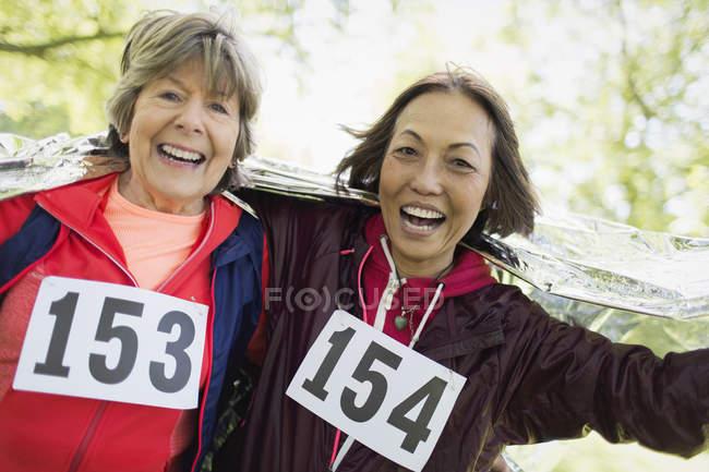 Портрет улыбающейся, уверенной в себе активной пожилой женщины, заканчивающей спортивную гонку, завернутой в тепловое одеяло — стоковое фото