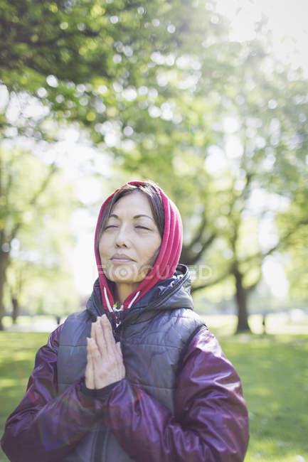 Mulher de sênior ativa Serena meditando no parque ensolarado — Fotografia de Stock