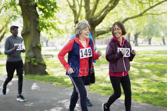 Active senior women friends power walking sports race in park — Stock Photo