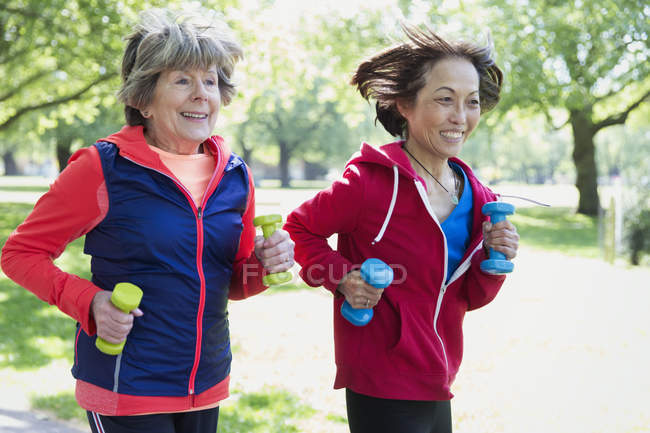 Active senior women friends jogging with hand weights in park — Stock Photo