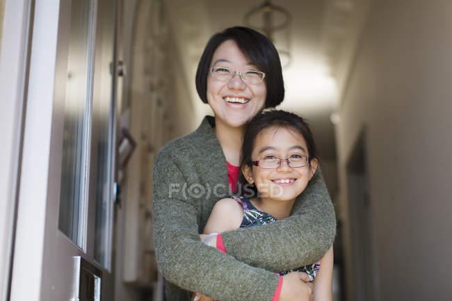 Portrait happy, affectionate mother and daughter hugging in doorway — Stock Photo