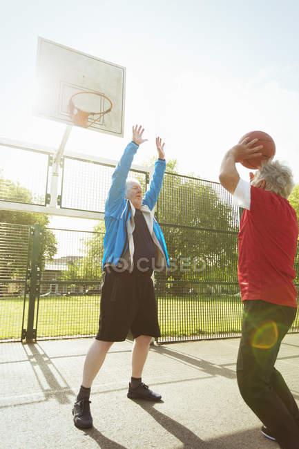 Hombres mayores activos jugando baloncesto en Sunny Park - foto de stock