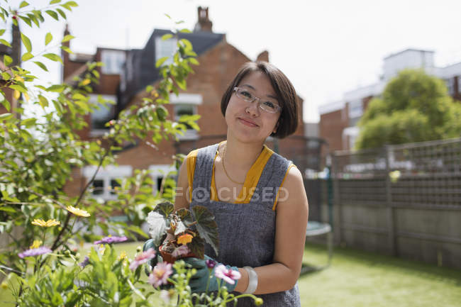 Portrait smiling woman gardening in sunny yard — Stock Photo