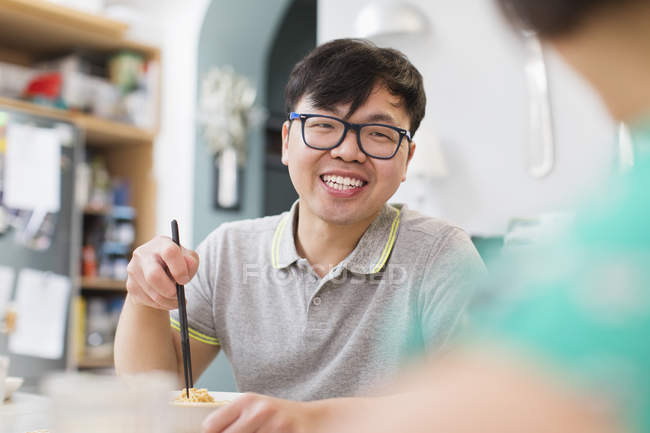 Tagliatelle di uomo felice mangiare con le bacchette — Foto stock