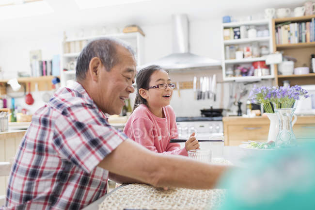 Grandfather and granddaughter at kitchen table — Stock Photo