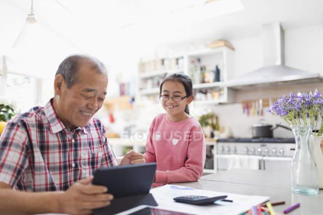 Grand-père et petite-fille utilisant une tablette numérique dans la cuisine — Photo de stock