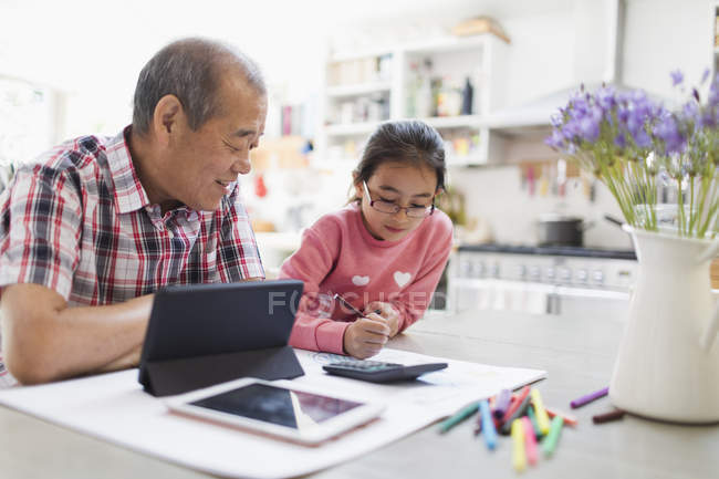Grand-père et petite-fille colorier et utiliser une tablette numérique dans la cuisine — Photo de stock