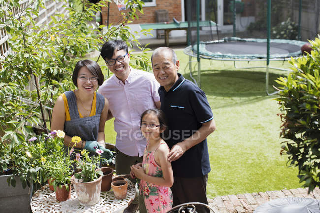 Portrait smiling multi-generation family gardening, potting flowers in sunny yard — Stock Photo