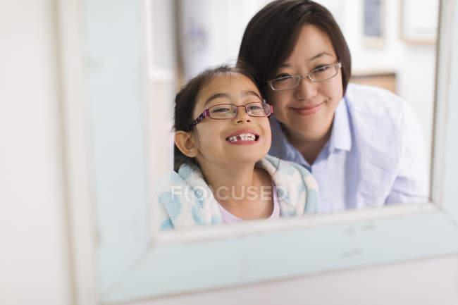 Mãe assistindo filha mostrando dentes no espelho do banheiro — Fotografia de Stock