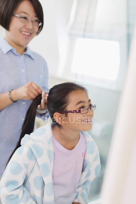 Mother fixing daughters hair in bathroom — Foto stock