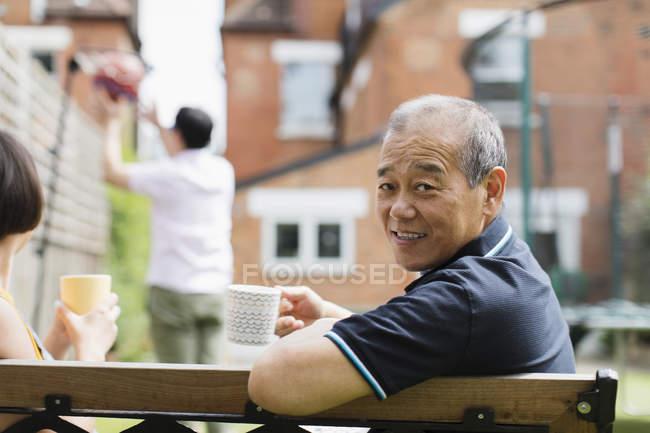 Портрет улыбающийся пожилой мужчина пьет чай с семьей во дворе — стоковое фото